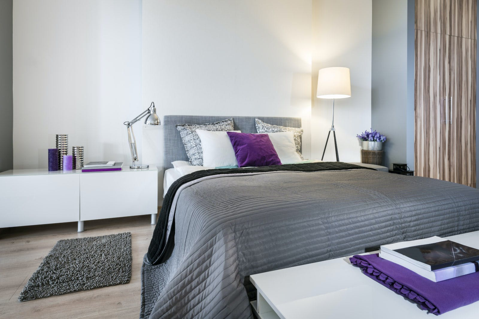 Bedroom interior with gray bed and white walls