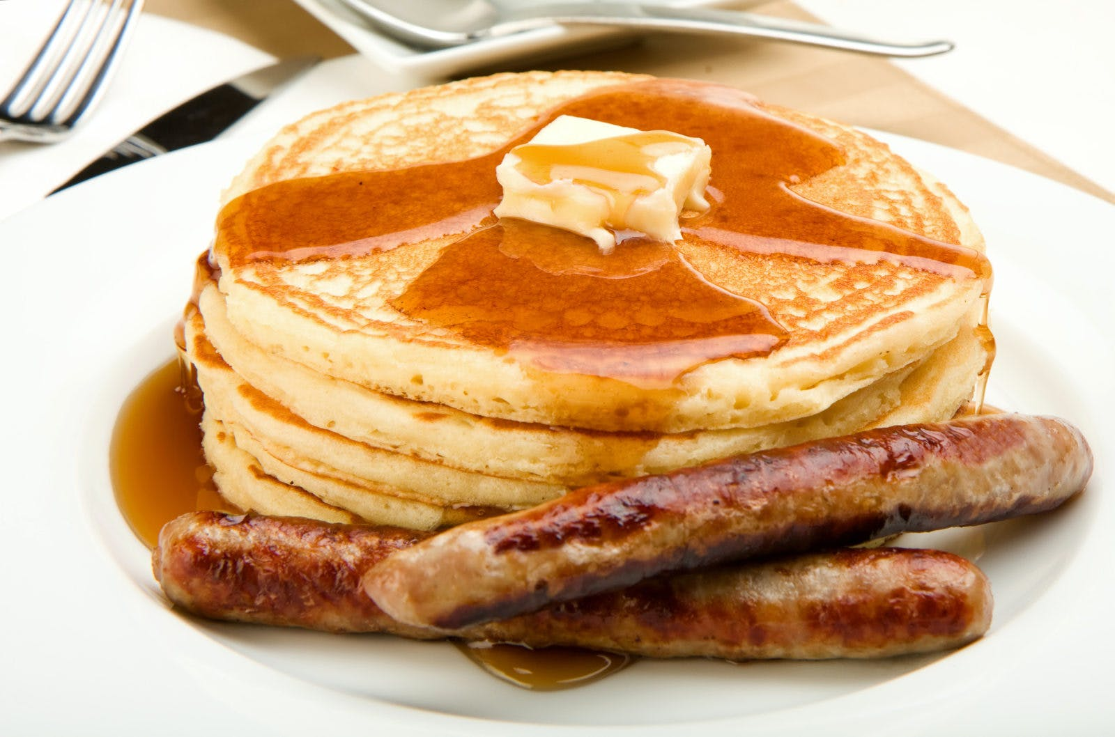 Breakfast of coffee pancakes and sausage with maple syrup